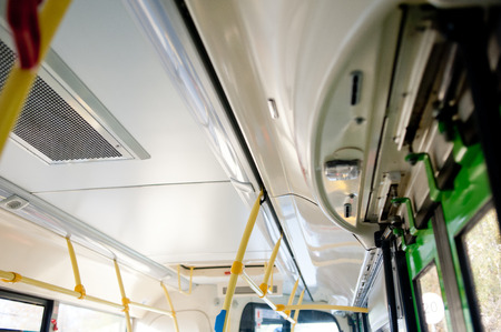 Public Bus Interior -- with yellow plastic handles for stand up support Stock Photo