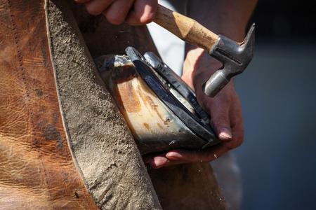 smithery: hammering the horseshoe close up
