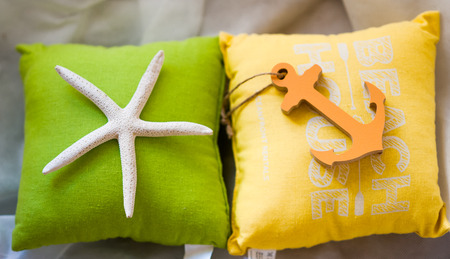 cushion sea star: Holiday summertime travel concept - small toy pillows with starfish and anchor Stock Photo