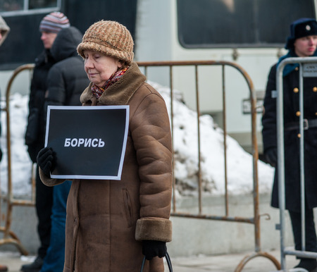 Moscow - Russia, February 25th, march of memory of Boris Nemtsov: Senior lady with the table which says: Fight. Paddy vagons, fences and soldiers on the background