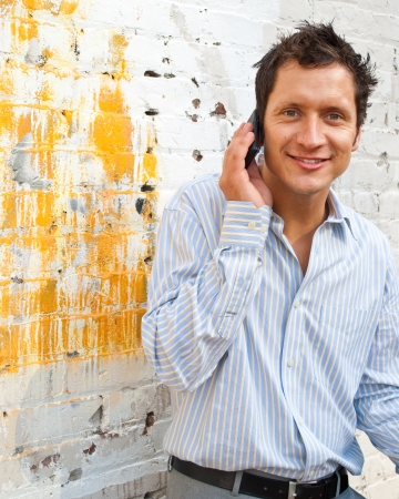Man in Casual Business Attire Talking on the Phone Outside photo