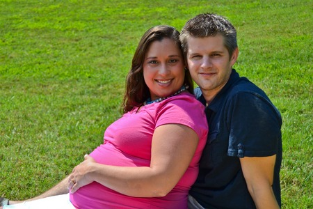 two people fertility: Expectant Couple Sitting in the Grass