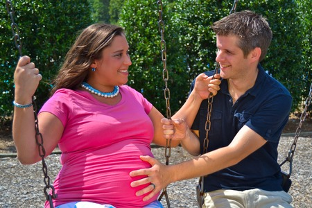 two people fertility: Expectant Couple on a Swing Set