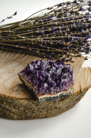 esoteric: Raw amethyst rock with bunch of aromatic lavender flowers on natural wood rustic crystal ametist esoteric