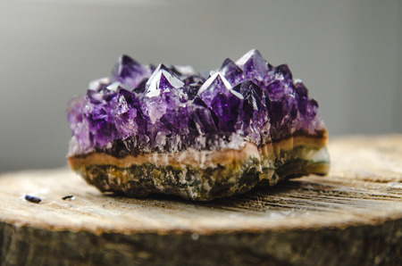 esoteric: Raw violet amethyst rock with reflection on natural wood macro crystal  ametist esoteric
