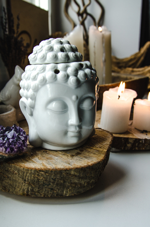 esoteric: spiritual ritual  meditating face of Buddha ametist candles on old wooden background Esoteric