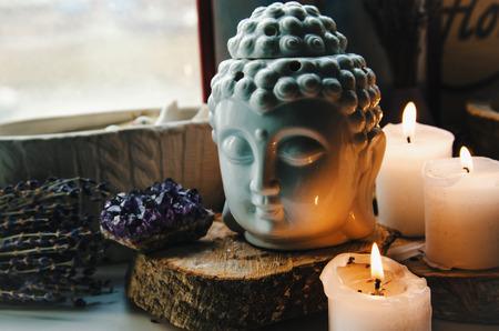 spiritueel ritueel mediteren gezicht van Boeddha ametist kaarsen op oude houten achtergrond Esoteric tonale curves kleur