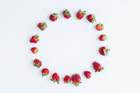 Oval frame of strawberries on white background. Flat lay, top view. Imagens