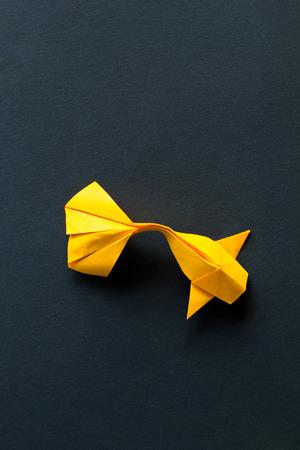 Handmade paper craft origami gold koi carp fish on black background.Top view