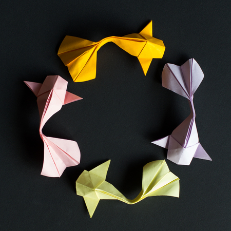 Oval frame figure of handmade paper craft origami gold koi carp fishes on black background.Top view, size 1*1