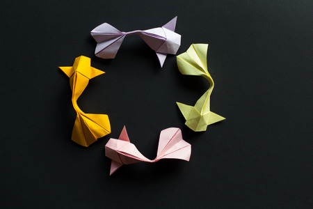 Oval frame figure of handmade paper craft origami gold koi carp fishes on black background.Top view Stock Photo