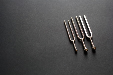 Three tuning forks on a black background