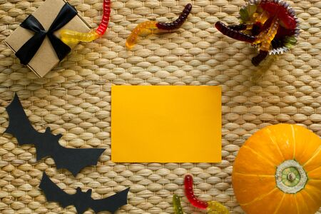 Halloween holiday background with pumpkin, worm candy, ghost, bat. View from above. Nice for mockup. Stock Photo