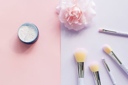 Five makeup brushes with lettering on the handle and mineral powder in a blue jar, bobby pin in the form of a pink flower on pink and purple background. Have copy space.