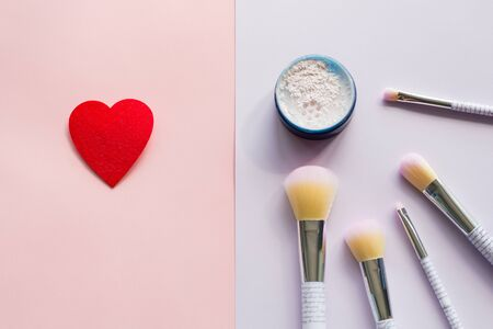 Five makeup brushes with lettering on the handle and mineral powder in a blue jar, red felt brooch in the form of a heart on pink and purple background. Have copy space.