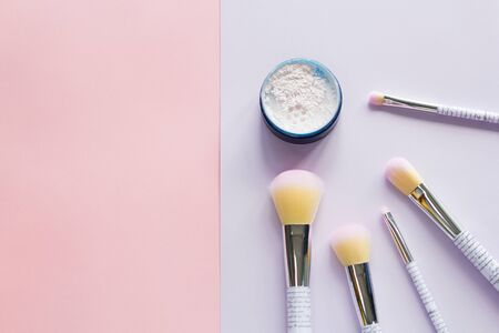 Five makeup brushes with lettering on the handle and mineral powder in a blue jar on pink and purple background. Have copy space.