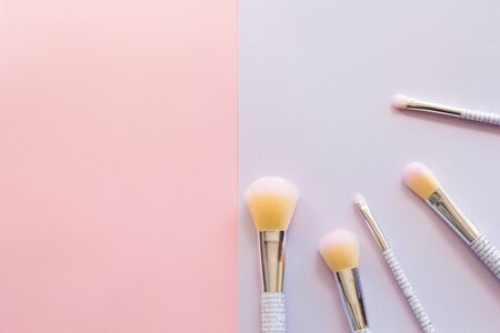 Five makeup brushes with lettering on the handle on pink and purple background. Have copy space.