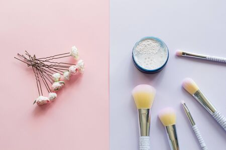 Five makeup brushes with lettering on the handle and mineral powder in a blue jar, wedding hairpins for hair with handmade peonies made of plastic on pink and purple background. Have copy space.