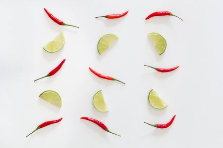 Pattern of red hot chili peppers and sliced limes on a white background. Asian species.Top view.