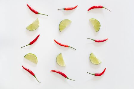 Pattern of red hot chili peppers and sliced limes on a white background. Asian species.