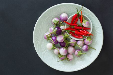 Purple Thai eggplants and hot chili peppers on a green plates on a black background. Asian food. 스톡 콘텐츠