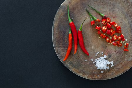 Red hot chili peppers and sliced peppers on a wooden cutting board with salt crystals nearby on a black background. Asian species.