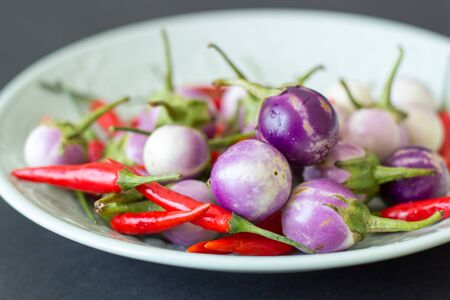 Purple Thai eggplants and hot chili peppers on a green plate on a black background. Asian food.