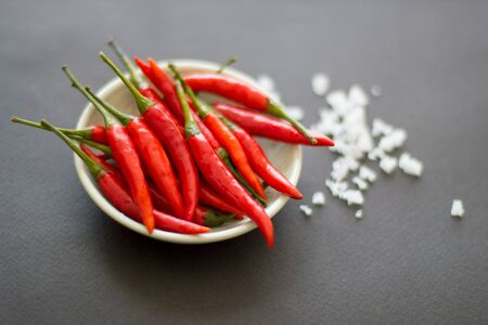 Red hot chili peppers on a green plate with salt crystals nearby on a black background. Asian species. 스톡 콘텐츠