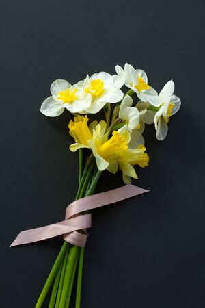 Lovely bouquet of white and yellow narcissus with a pink ribbon on a black background