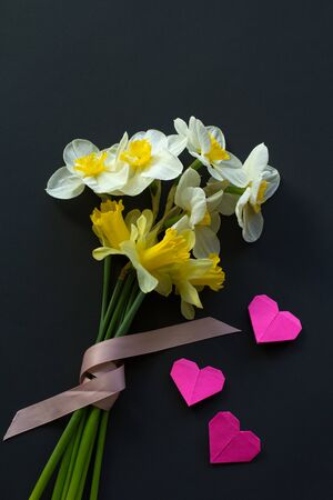 Lovely bouquet of white and yellow narcissus with a pink ribbon and three pink origami hearts on a black background