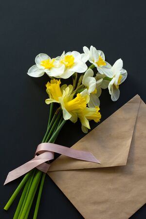 Lovely bouquet of white and yellow narcissus with a pink ribbon and craft brown envelope on a black background