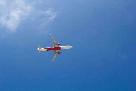Passenger plane flying in the blue sunny sky 스톡 콘텐츠
