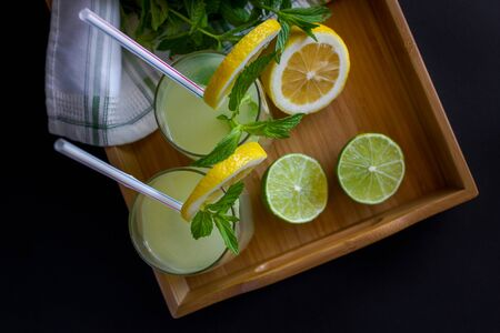 Homemade citrus lemonade in glasses with straws with mint leaves and a bunch of mint, lemons, limes on a bamboo tray and whte towel on a black background. Top view