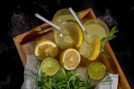 Homemade citrus lemonade in glasses with straws with mint leaves and a bunch of mint, lemons, limes on a bamboo tray and whte towel on a black background with charming with sunspots. Top view