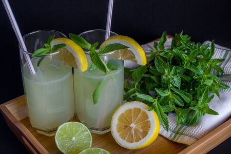 Homemade citrus lemonade in glasses with straws with mint leaves and a bunch of mint, lemons, limes on a bamboo tray and whte towel on a black background. Close up 스톡 콘텐츠