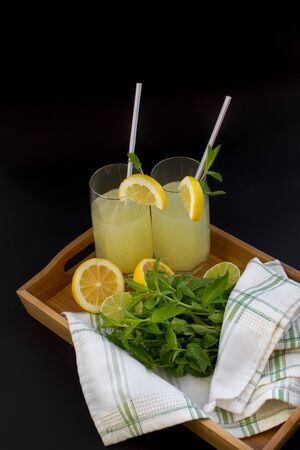 Homemade citrus lemonade in glasses with straws with mint leaves and a bunch of mint, lemons, limes on a bamboo tray and whte towel on a black background. Front view