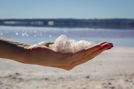 Female hand holding natural salt crystals on the background of a salt lake, side view close up