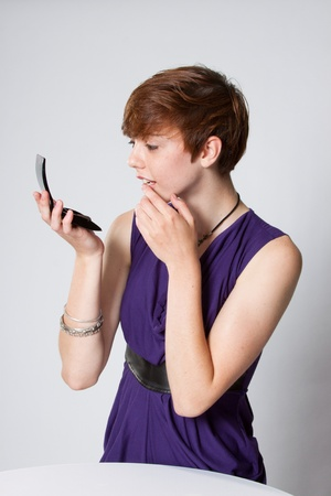 Young woman putting on make up. photo