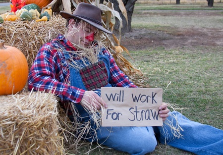Depressed and unemployed scarecrow panhandles. photo