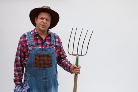 Hillbilly or farmer standing with a pitchfork.