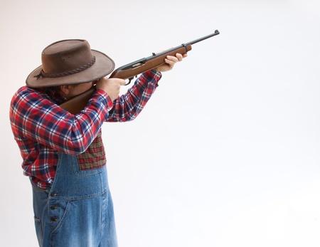 Hillbilly Farmer taking aim with gun or hunting.