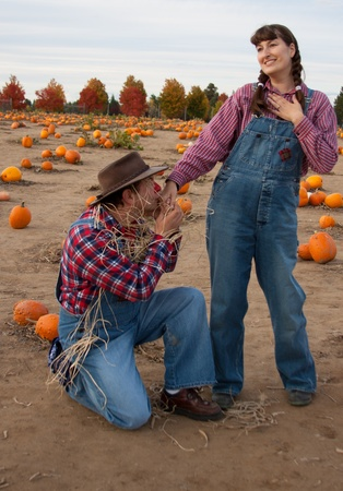 Scarecrow flirts with farmers wife or daughter. Imagens