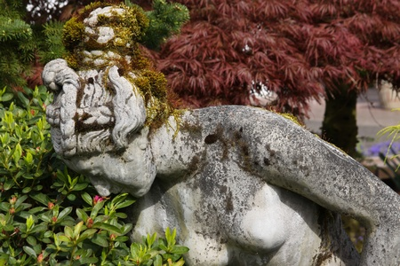 A statue that is smelling the flowers in the garden