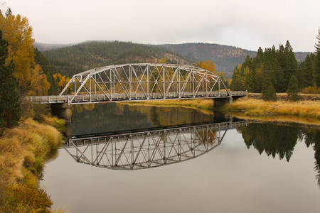 A bridge over tranquil water in autumn  Stock Photo