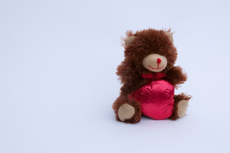 valentine s day teddy bear: A Valentine s Day Teddy Bear with a red covered chocolate heart  Stock Photo