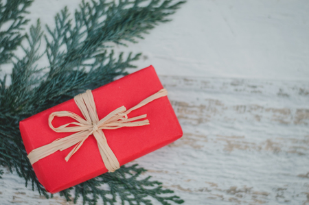 Christmas background with shoots twigs of thuja and scarlet a gift in packing on a white wooden background Stock Photo