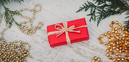 Christmas background with sprigs of shoots arborvitae, Christmas gold beads and gift in al the packing on a white wooden background