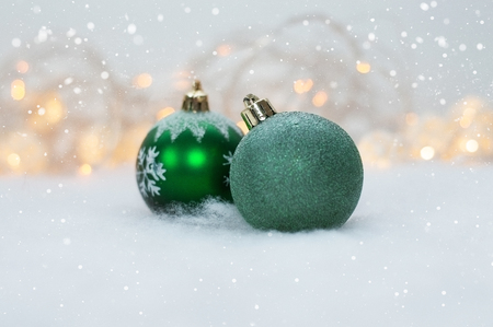 2 green Christmas ball on the background lights garland and faux snow