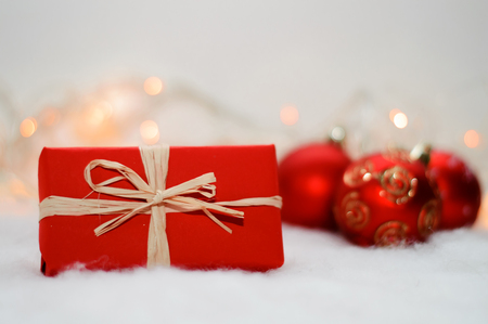 Christmas gift in red box on the background lights, red balls and artificial snow Stock Photo