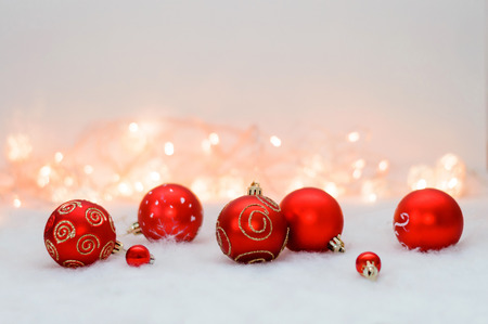 red Christmas balls on the background lights and artificial snow Stock Photo